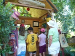 photo of 3 children and an adult looking at a booth with crafts
