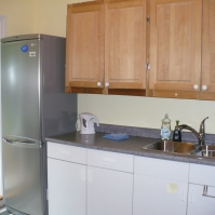 Photo of fridge/freezer, sink, and cupboards in the kitchen of Ahoy Guesthouse, Protection Island