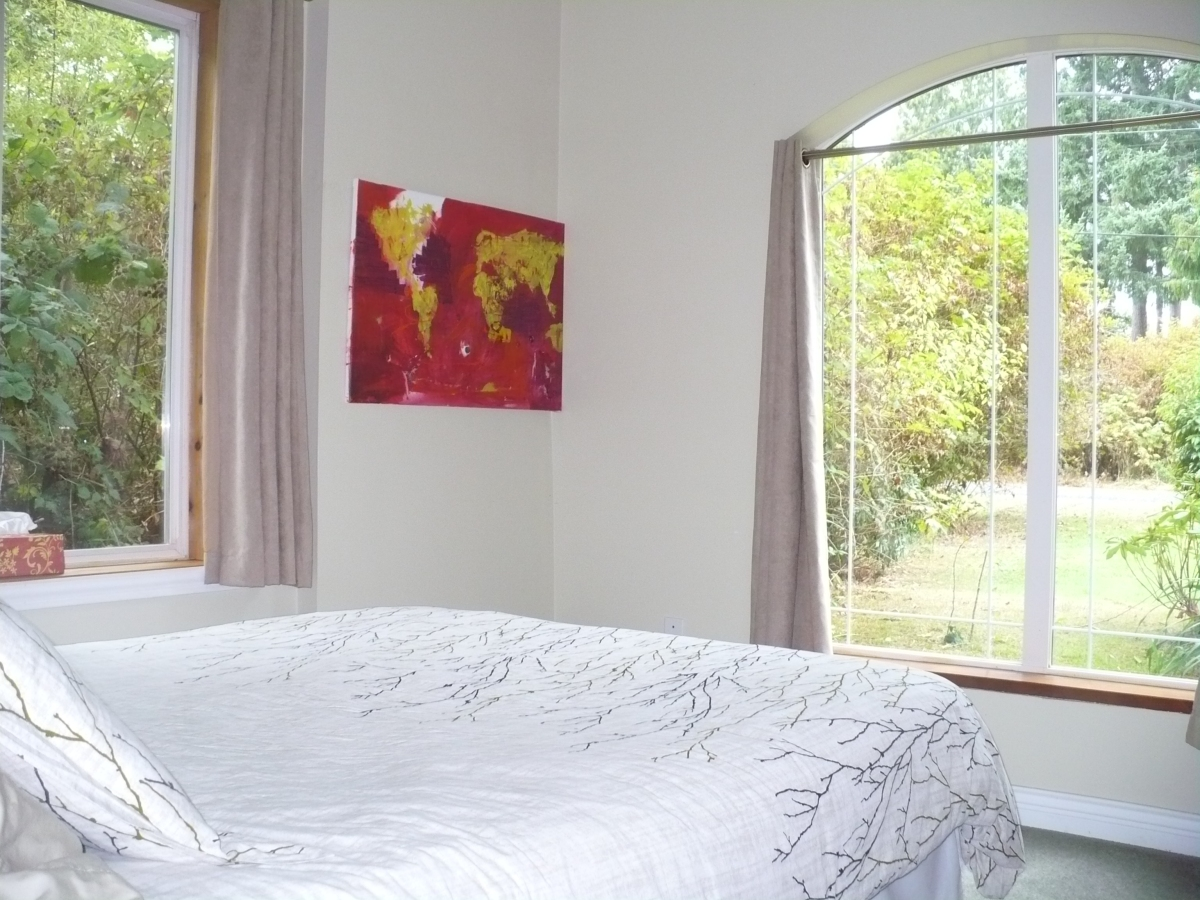 Photo of queen bed with tree patterned duvet, and two large windows with greenery outside at Ahoy Guesthouse, Protection Island