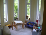 Photo of play area at Ahoy Guesthouse, Protection Island with windows all around, a kids' table ad chairs, and a variety of toys ad kids' instruments