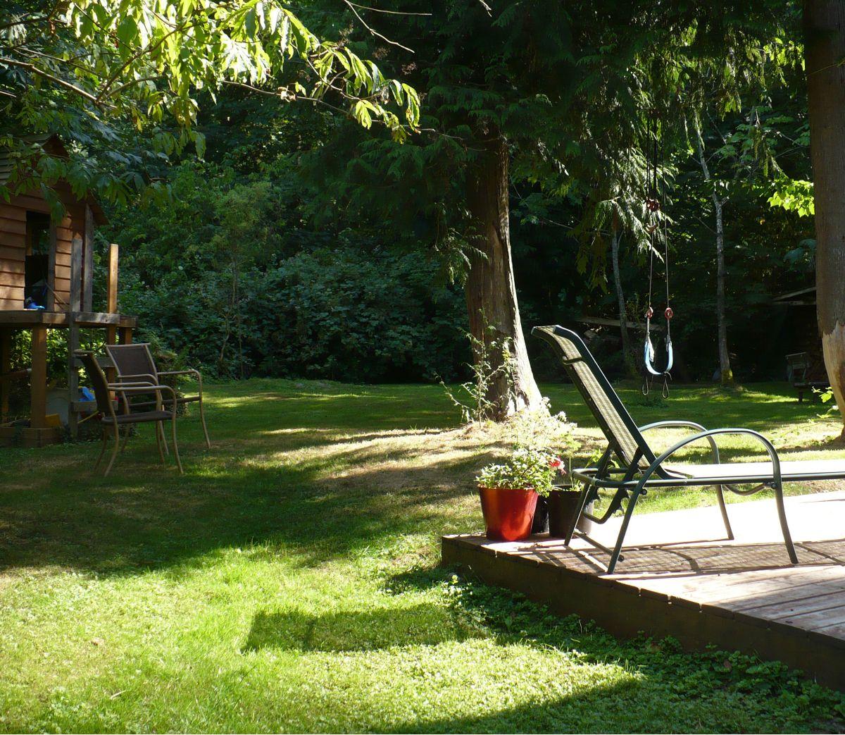 photo of treehouse, loungechair, and backyard