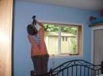 photp of a woman installing a curtain rod at Ahoy Guesthouse