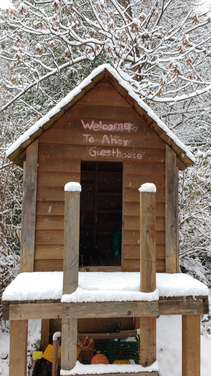 "Playhouse covered in snow with ""Welcome to Ahoy Guesthouse"" written on it."